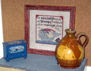 My whale jug on the right. I already had a miniature blanket chest my mother had painted with a folk art whale scene years ago, and I made a small sampler to complete my little whale tableau.